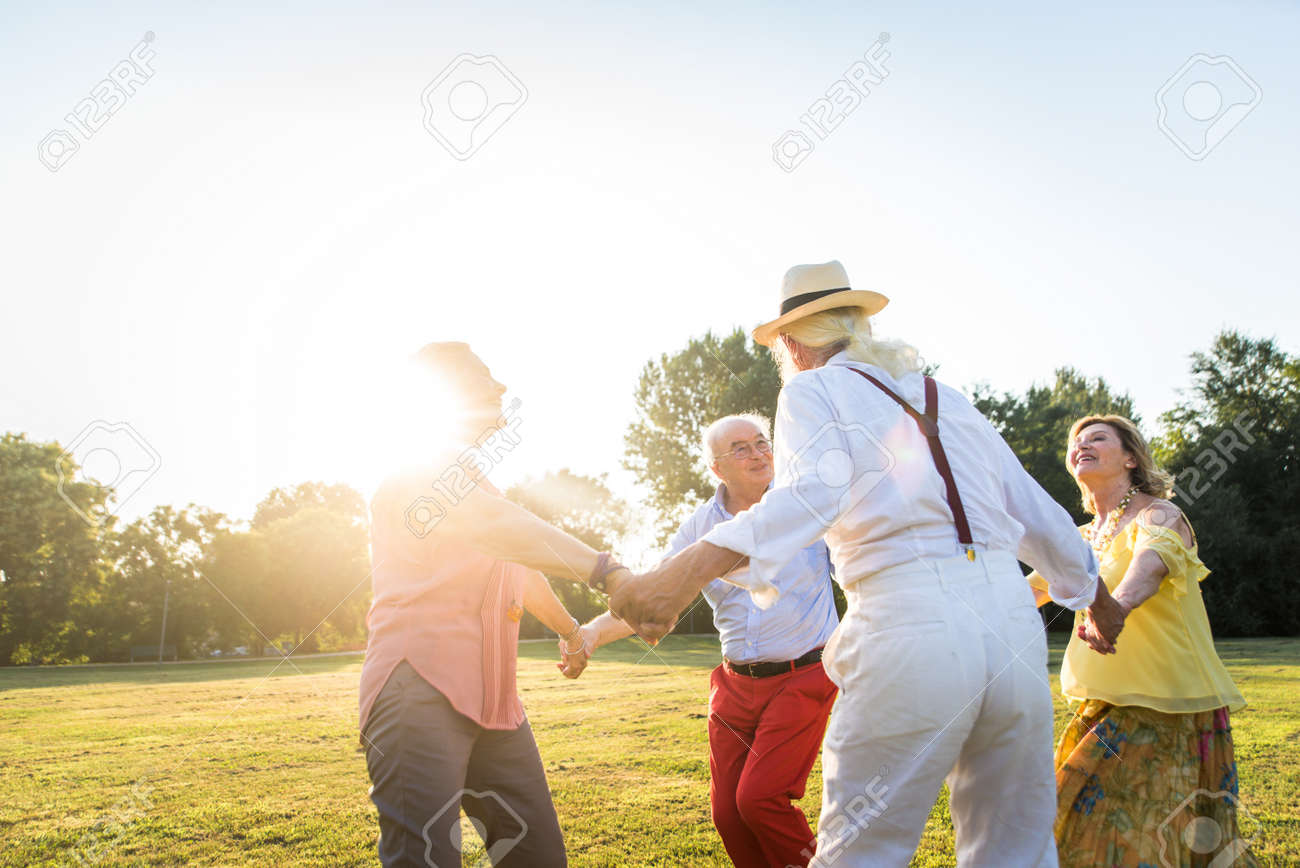 Group of youthful seniors having fun outdoors - Four pensioners bonding outdoors, concepts about lifestyle and elderly - 155170399