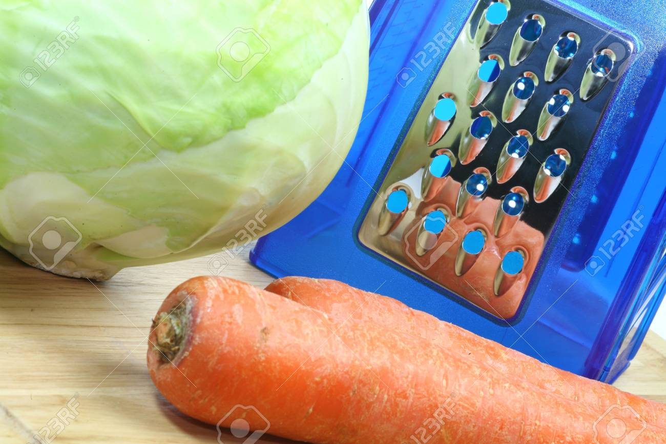 A steel grater and ingredients for coleslaw, cabbage and carrots ready to be grated. Stock Photo - 4477301