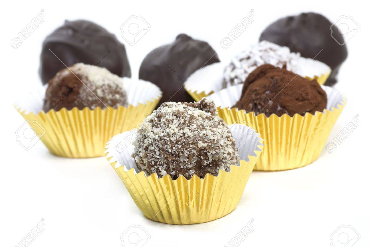 Homemade chocolate truffles with a variety of toppings such as cocoa, coconut, ground almonds. Each sitting in a gold foil cup. - 7903837