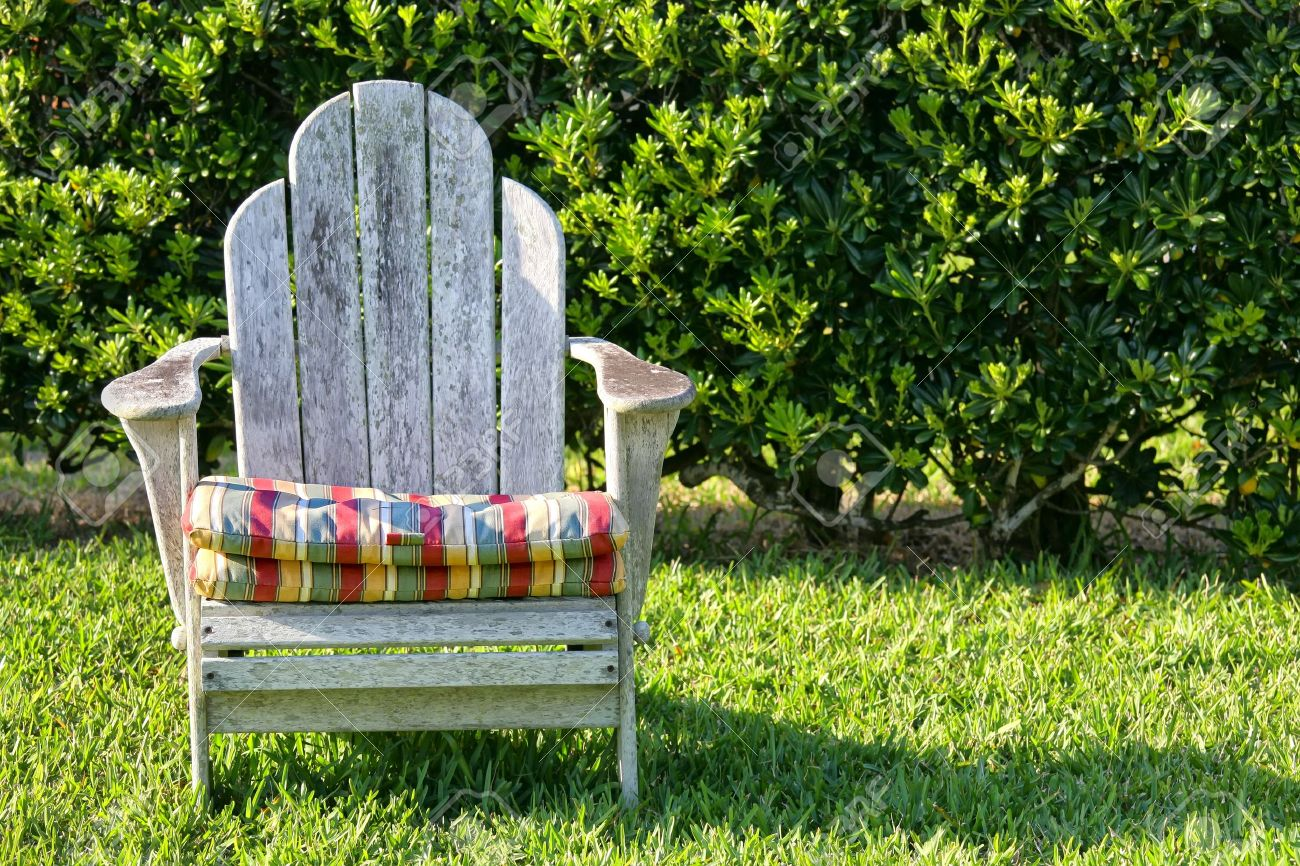 An Old Weathered Adirondack Chair In The Garden With A Hedge