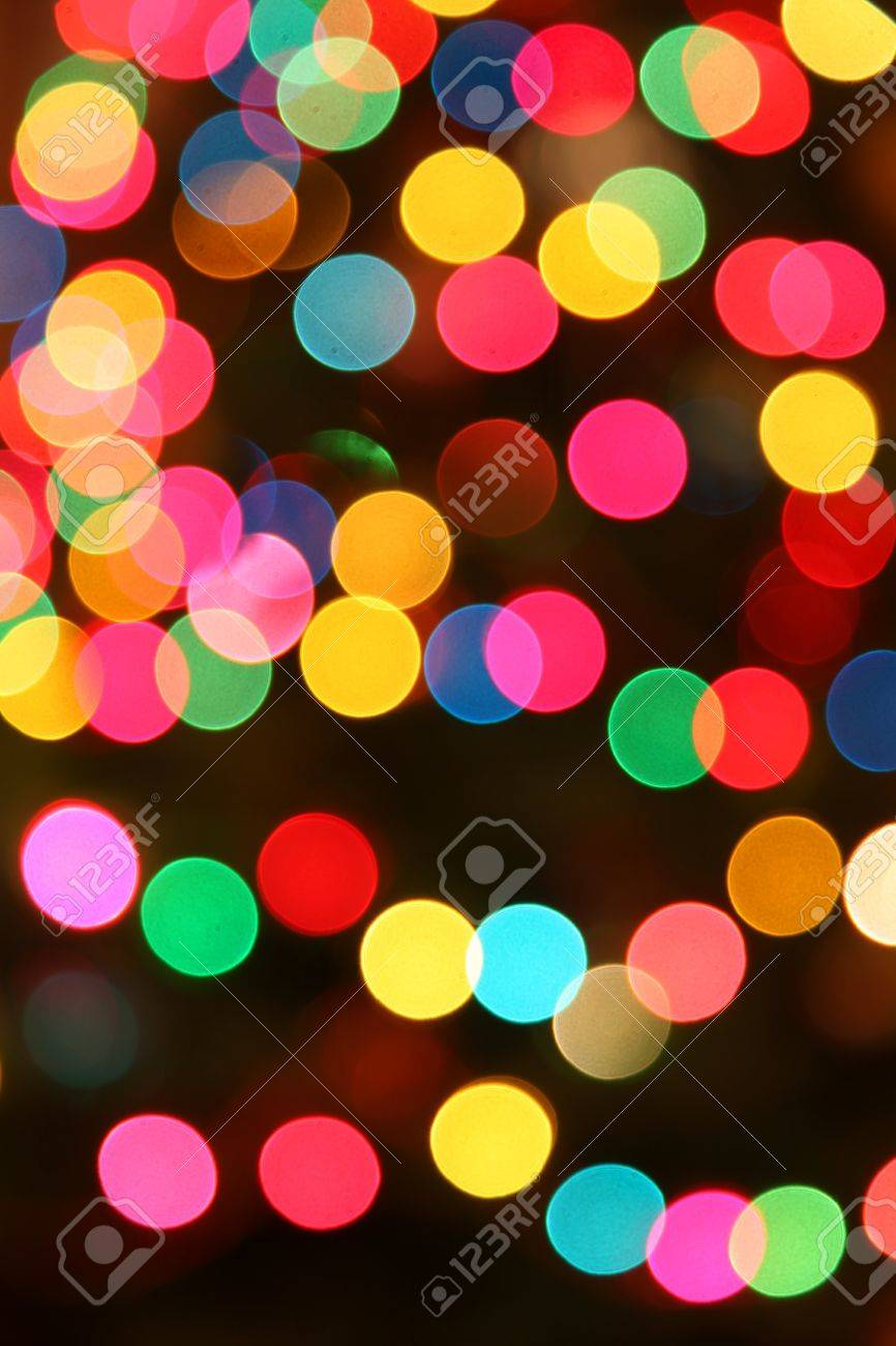 Multi colored Christmas lights out of focus on a dark background. - 9746915