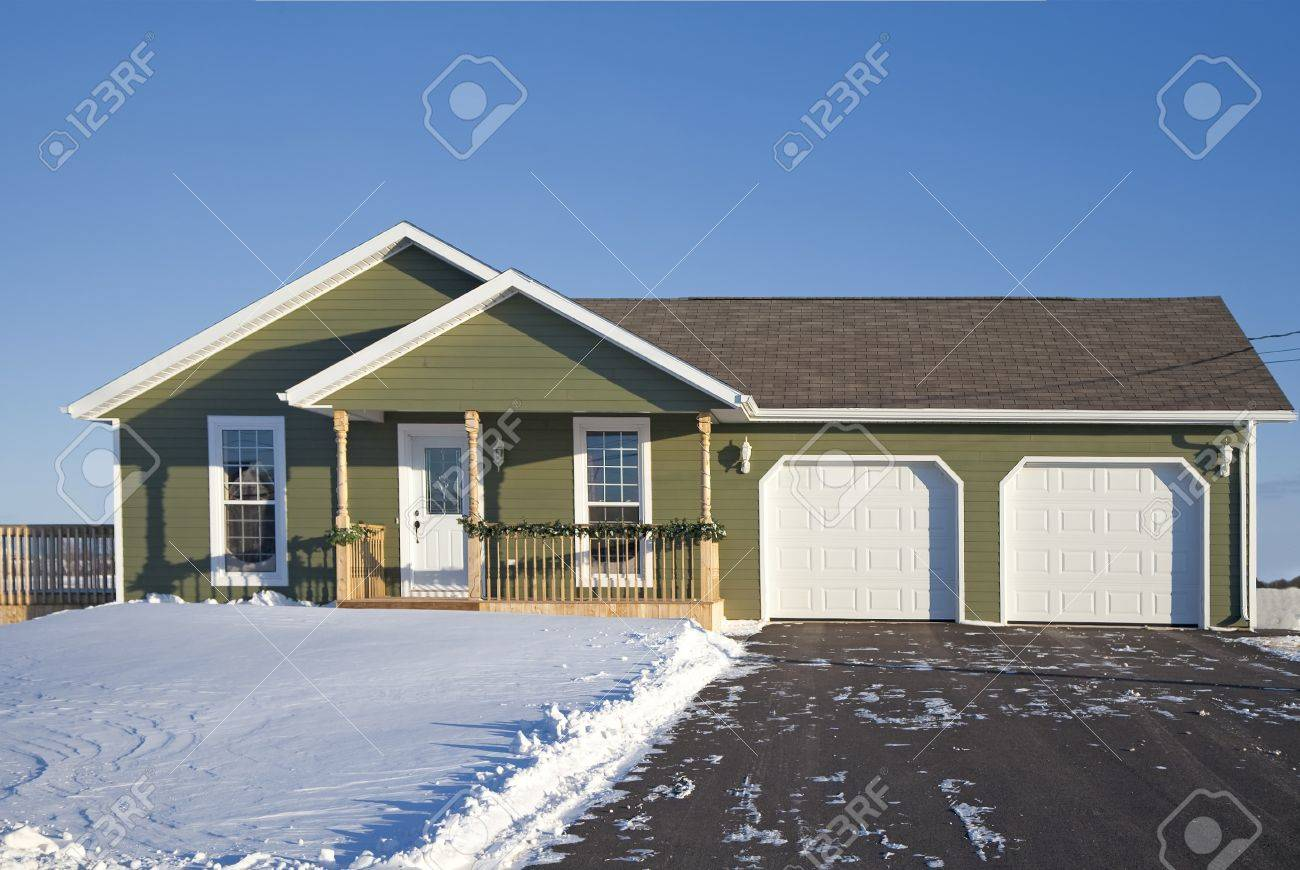 A small family home with a double car garage during the winter. Stock Photo  -