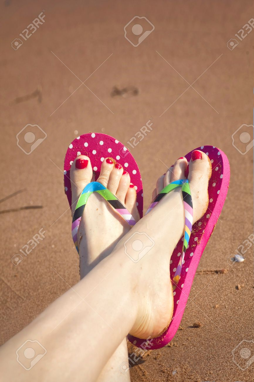 Painted toes and flip flops on a sandy beach Stock Photo - 12721501