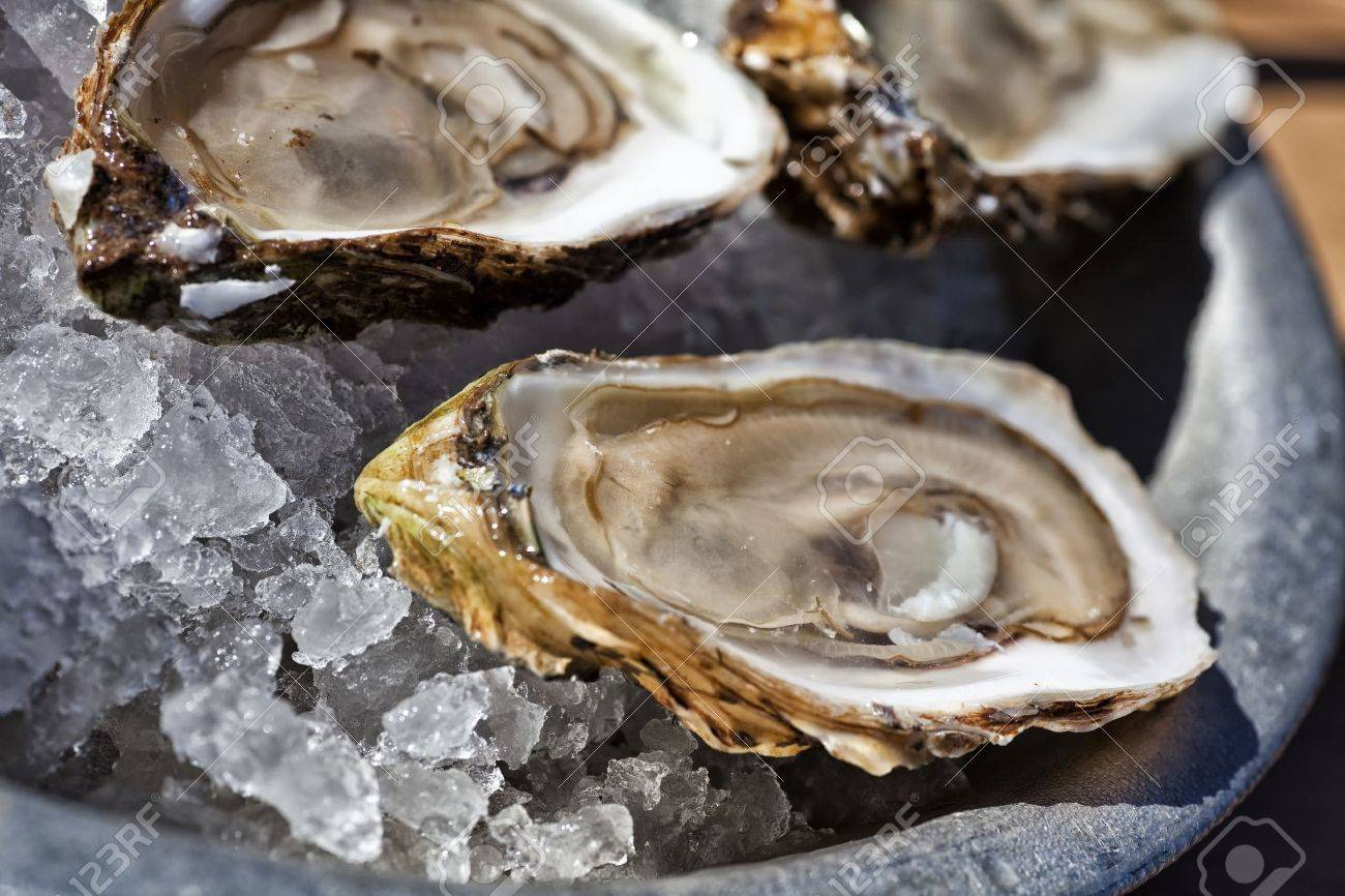 A platter of fresh raw oysters on ice at an outdoor cafe. - 12720880