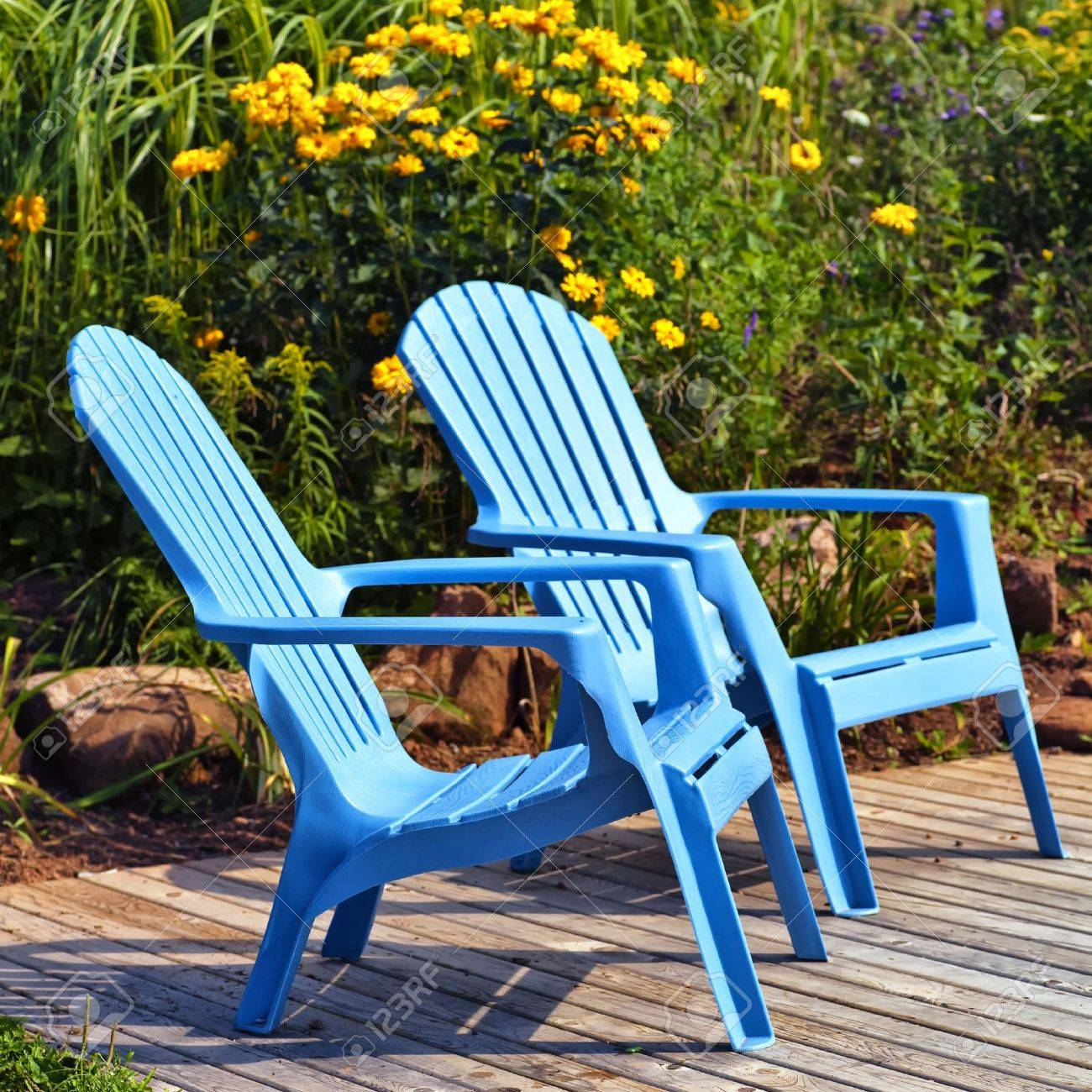 brilliant blue plastic outdoor adirondack chairs on the deck in a summer garden stock photo - Adirondack Chairs Plastic