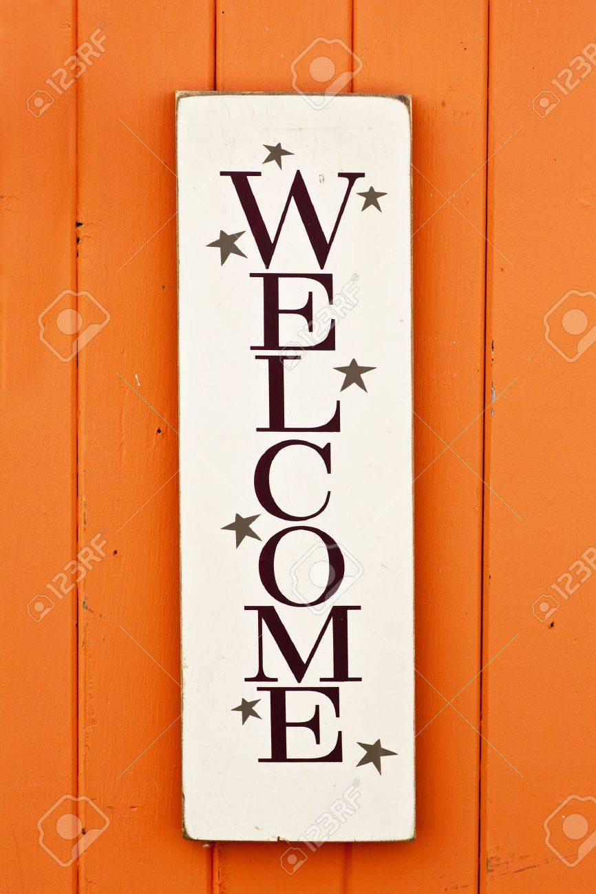 A folksy styled wooden 'Welcome' sign on the side of a brightly colored wooden building. Stock Photo - 13041378