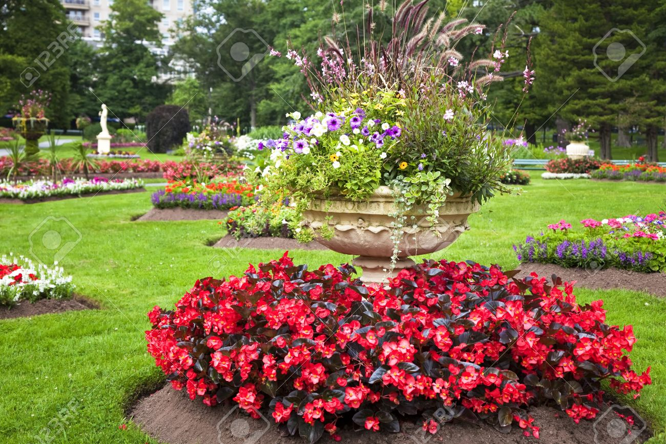 Ornate Large Cement Planters Filled With Annual Flowers In The Summer Garden.  Stock Photo