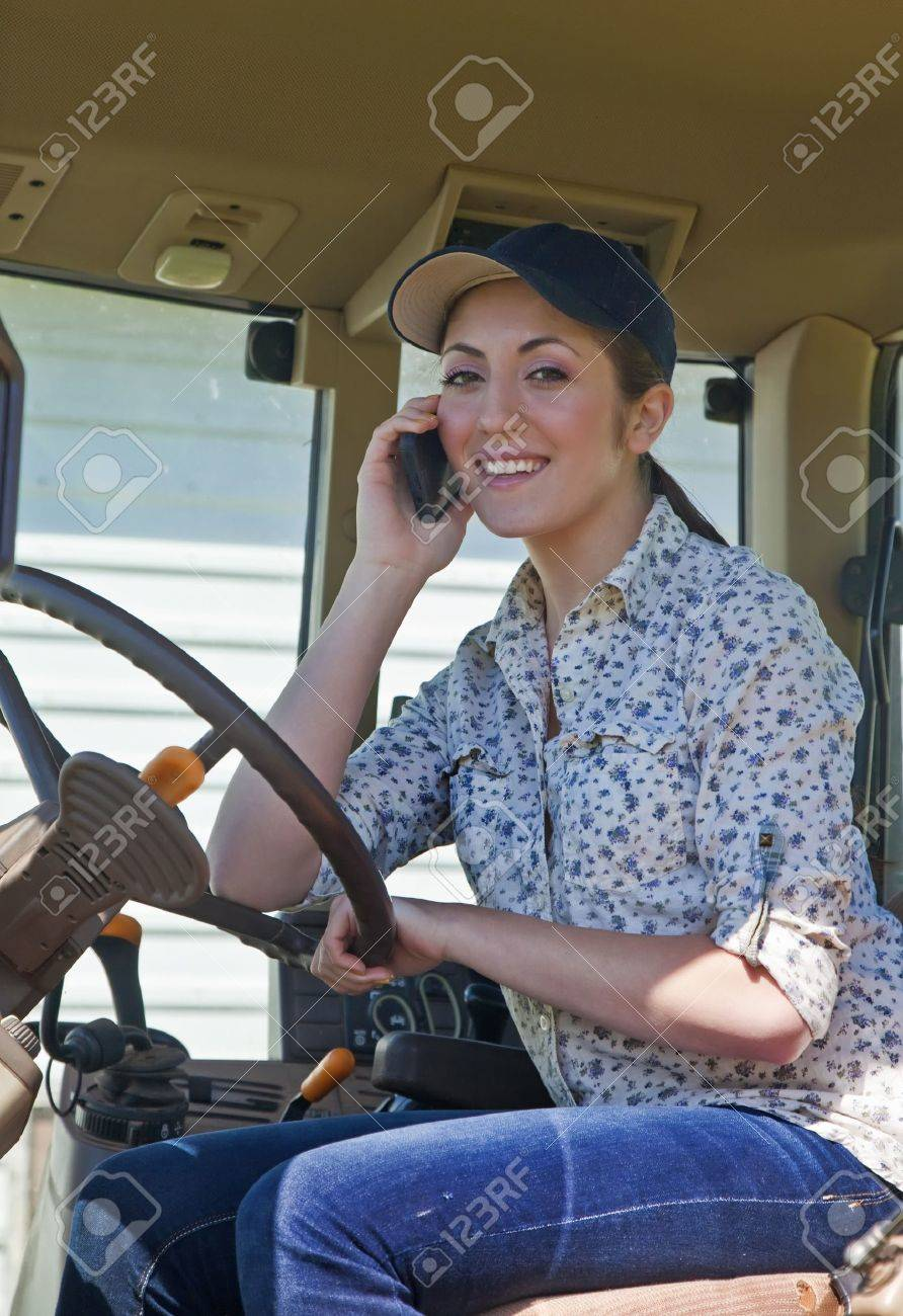 Young woman farmer speaking on her phone in the cab of her tractor Stock Photo - 13926528