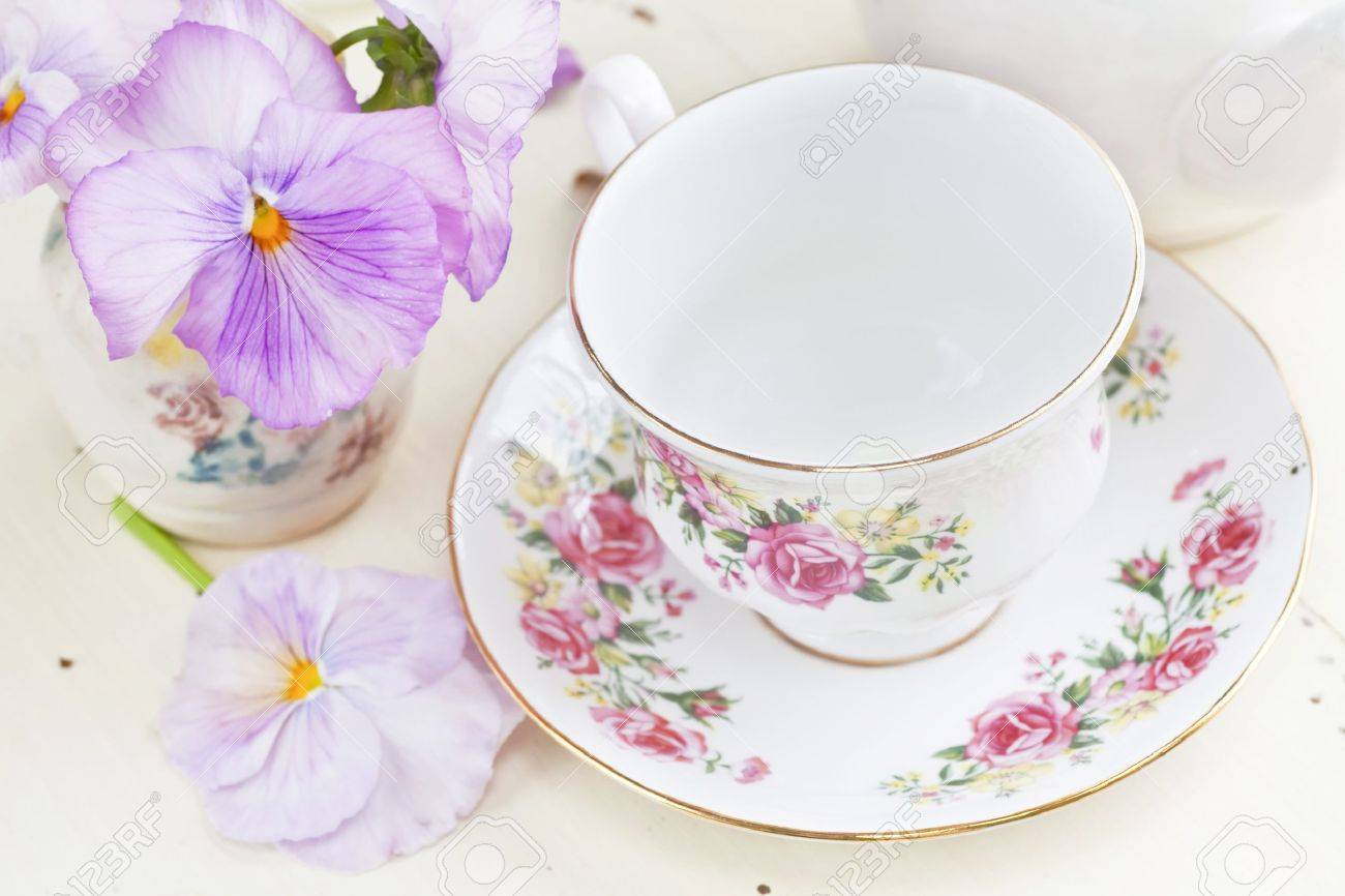 China teacup and pink springtime pansies by a morning window. Stock Photo - 13991421