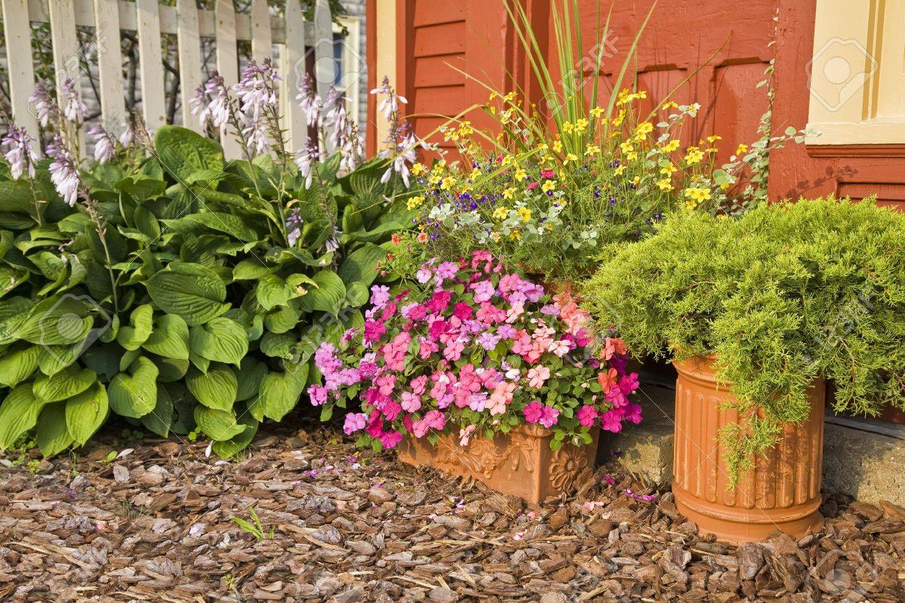 Planters used in the summer home garden filled with impatiens, juniper and other flowers. Stock Photo - 14049449