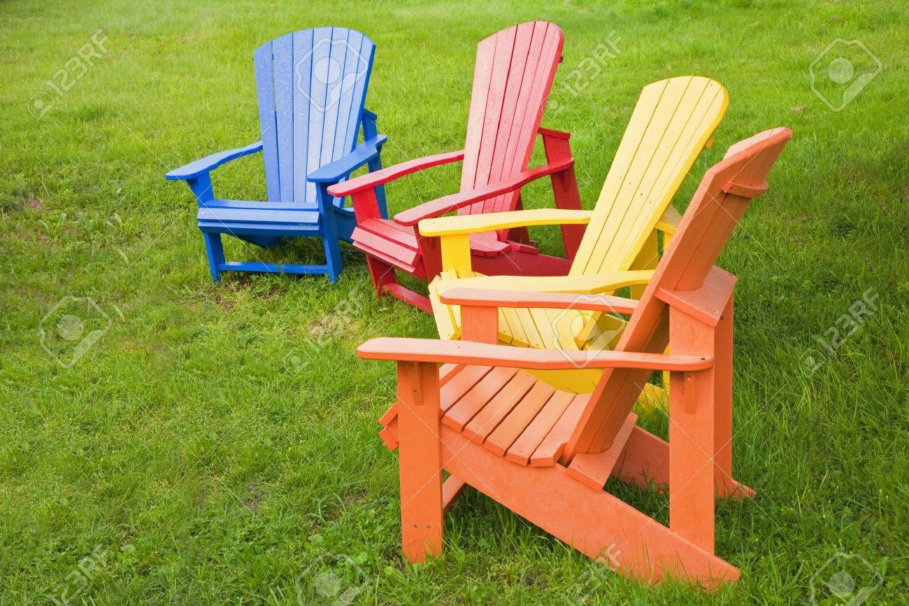 A Group Of Adirondack Chairs Painted In Brilliant Colors. Stock Photo    14049448