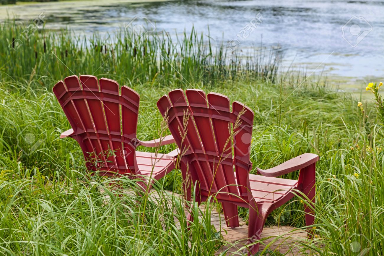 Red Plastic Adirondack Chairs Placed For A View Of The River. Stock Photo    20409631