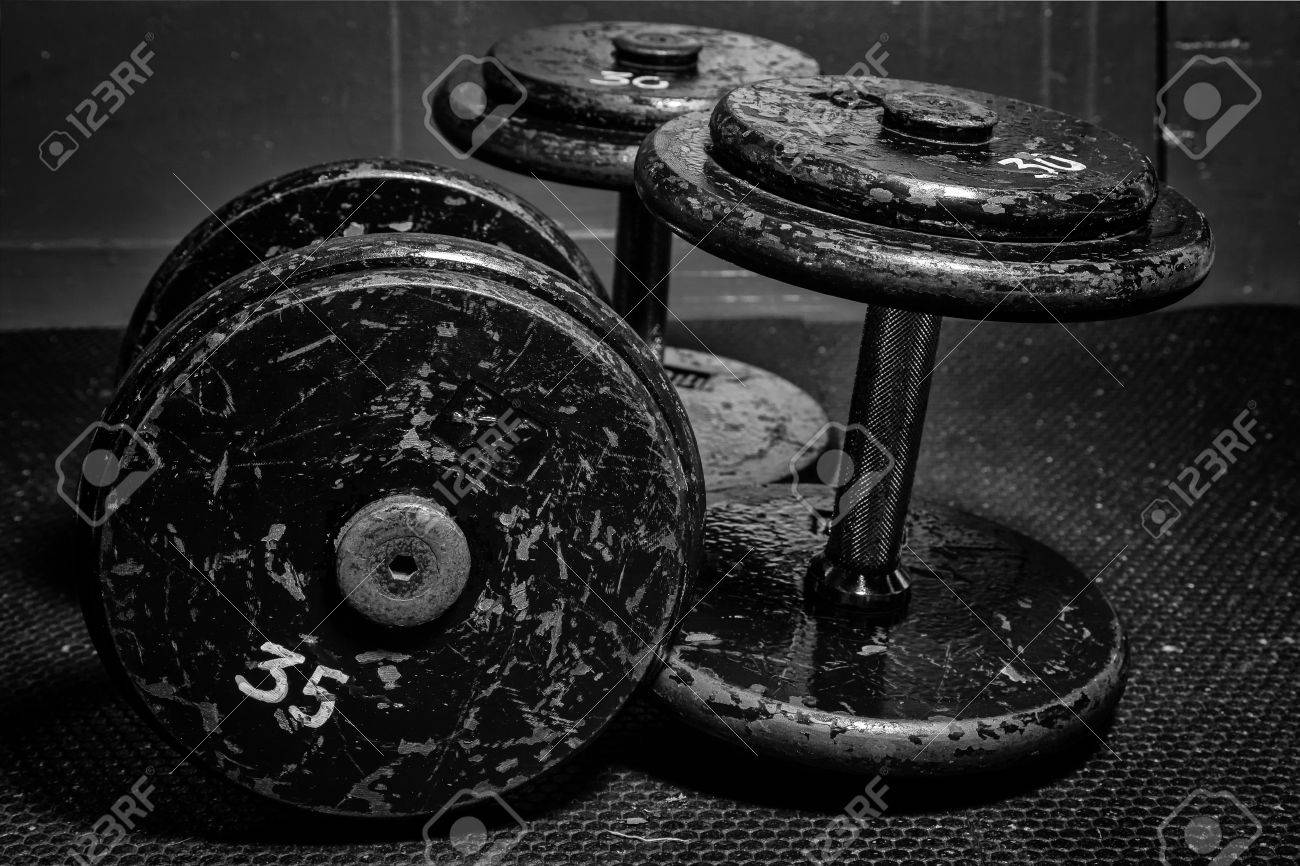 An old but well used set of dumbbells at the gym in black and white Stock Photo - 21856883