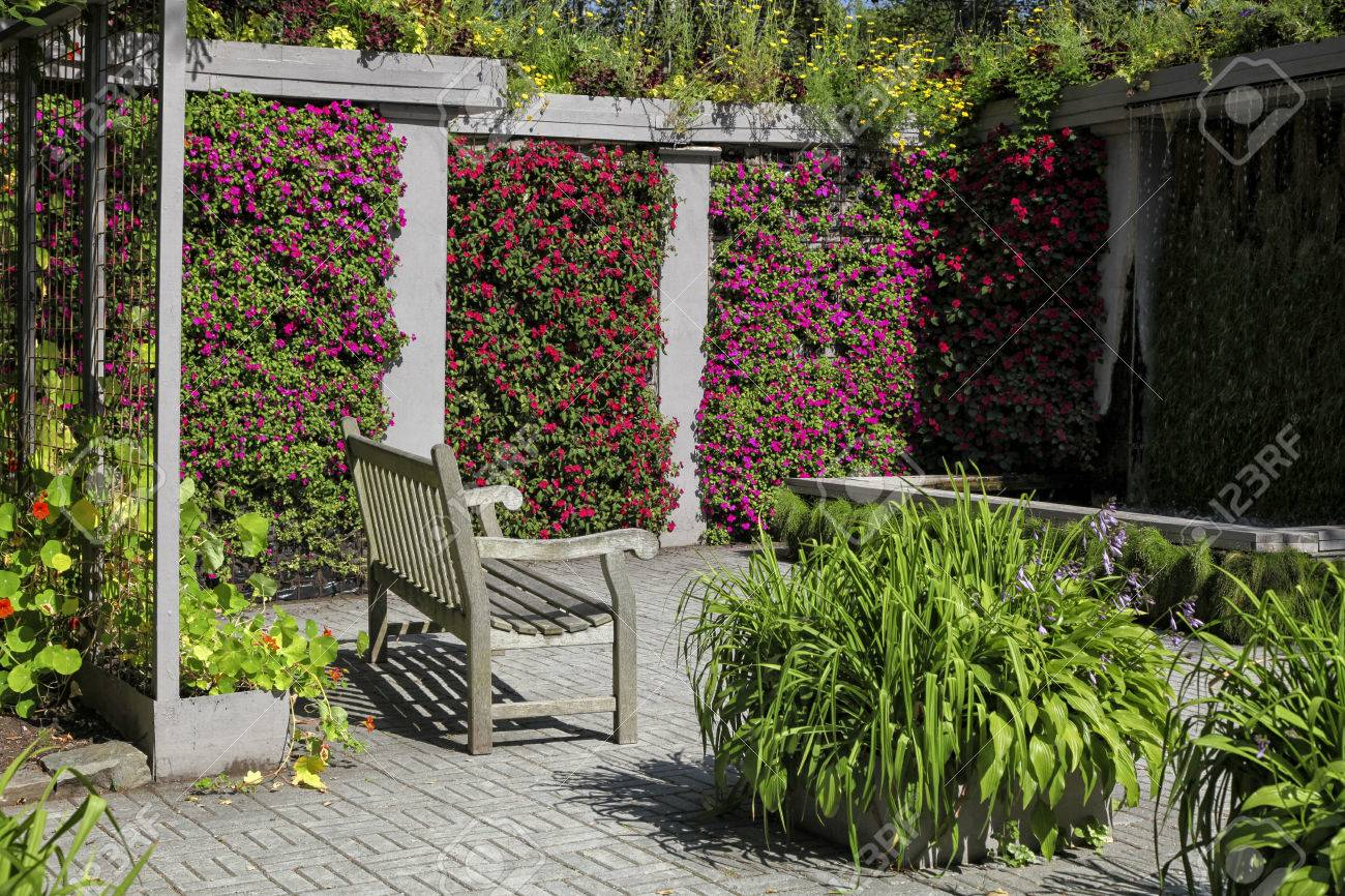 A wooden bench in a colorful garden niche with walls of vibrant flowering impatiens. Stock Photo - 24567918