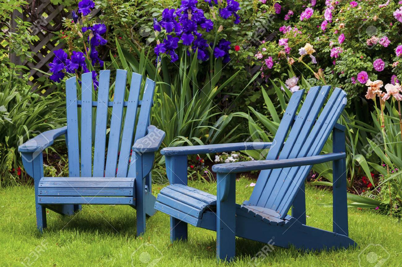 Blue back yard lawn chairs surrounded by a garden of flowers. Stock Photo - 26983567