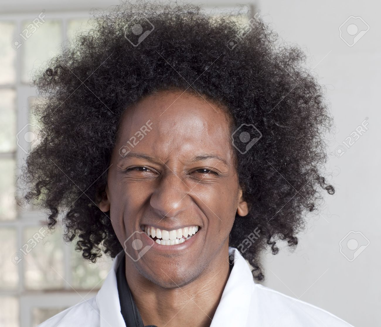 A young black man with an afro making various facial expressions while wearing a lab coat Stock Photo - 6649646
