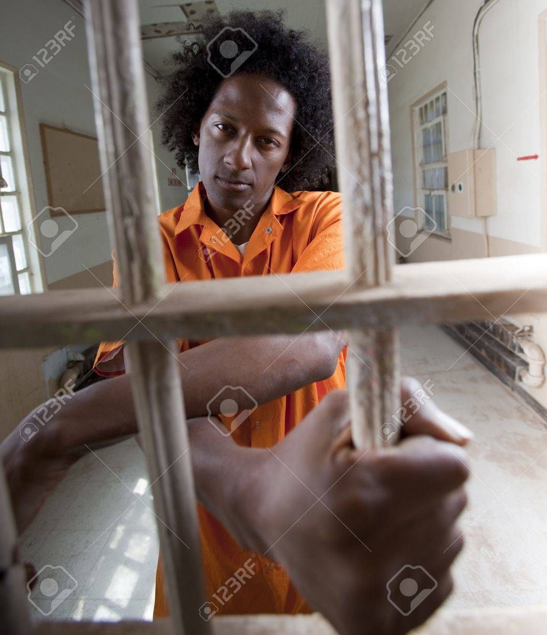 A black man with an afro making various faces and gestures inside a federal prison Stock Photo - 6649717