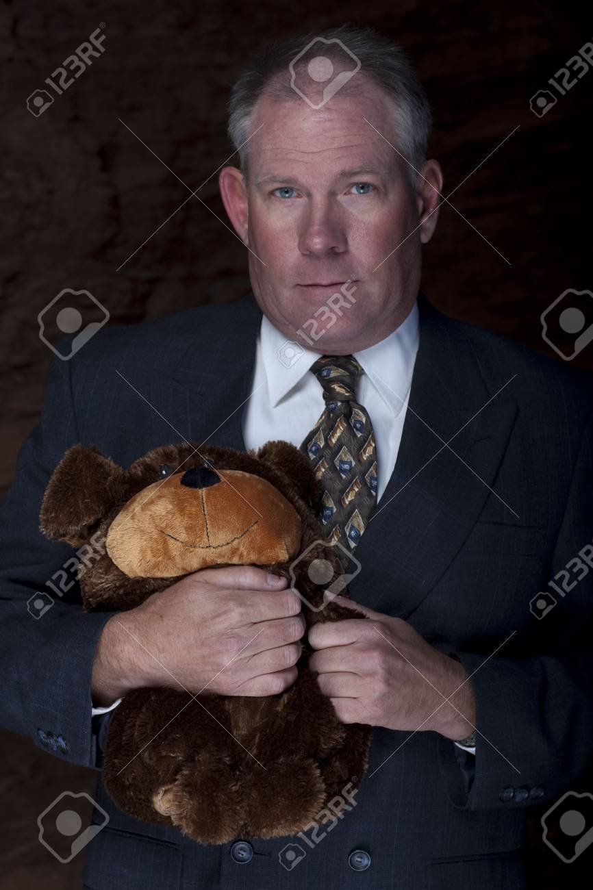 A businessman is clutches on to a teddy bear for security with a dark and rocky landscape in the background. Vertical shot. Stock Photo - 6781741