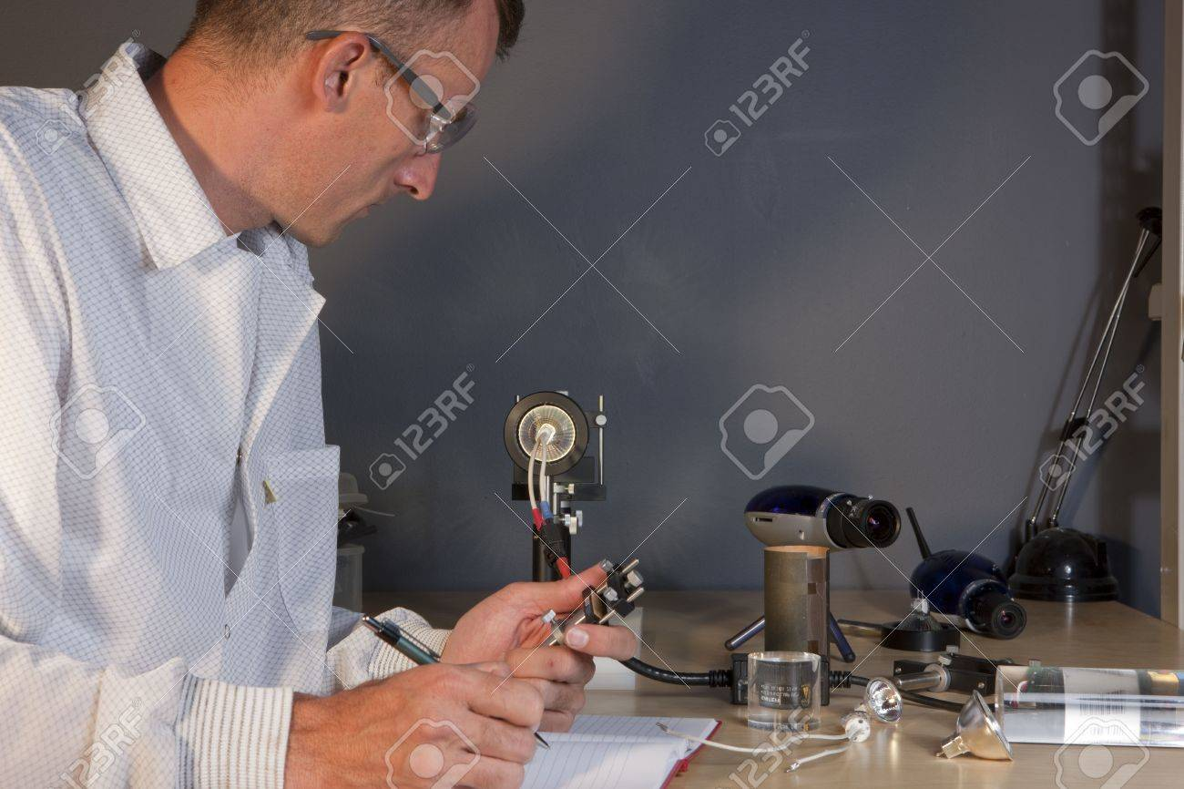 Cropped profile of a researcher in a lab coat and goggles, making notes on an experiment. He is surrounded by scientific equipment. Horizontal format. Stock Photo - 6781742
