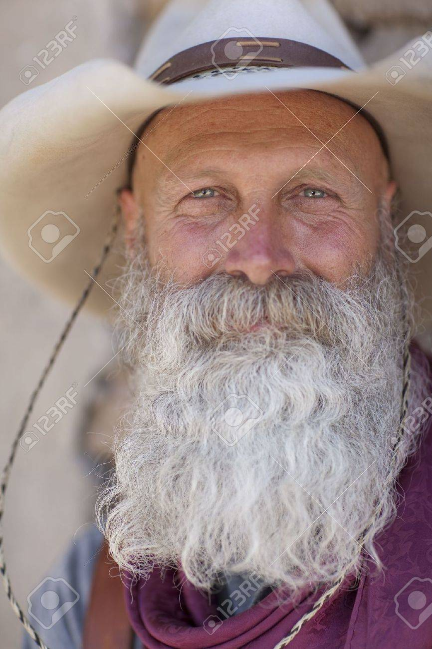 Portrait of an older man with a long white beard and cowboy hat smiling towards the camera. Vertical shot. Stock Photo - 6781745