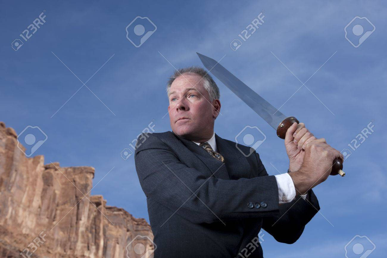 A businessman is holding a sword in an attack posture in a desert setting. Horizontal shot. Stock Photo - 6965404