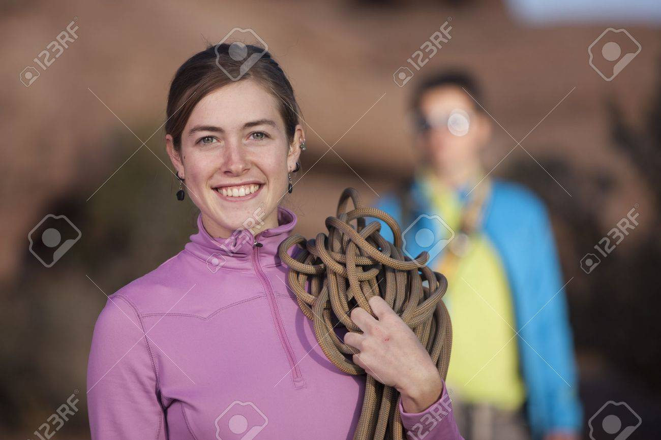 An attractive young woman is holding a rope used for mountain climbing. Her partner can be seen in the background. Vertical shot. Stock Photo - 6965429