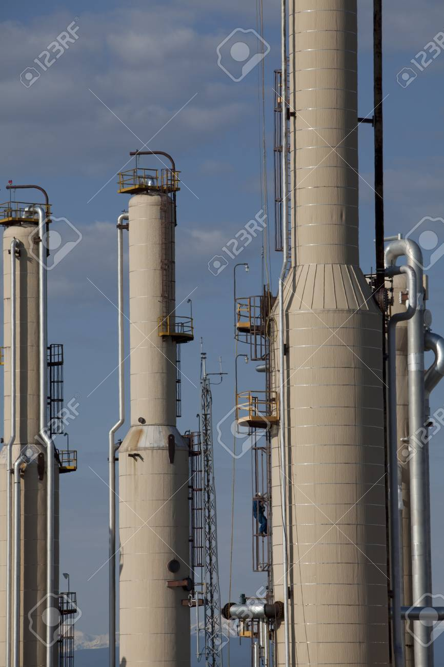 Piping and storage units in a gas compressor plant.  Mountains can be seen in the background. Vertical shot. Stock Photo - 6987164