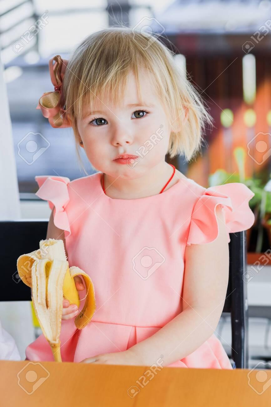 A girl eats a banana - 151016692