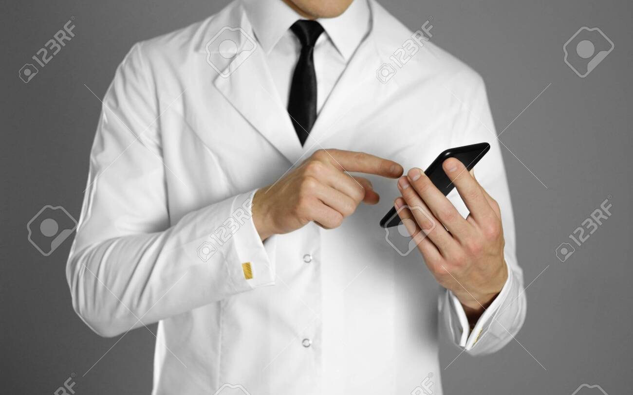 A doctor in a white shirt and black tie holds a smartphone. - 133206477