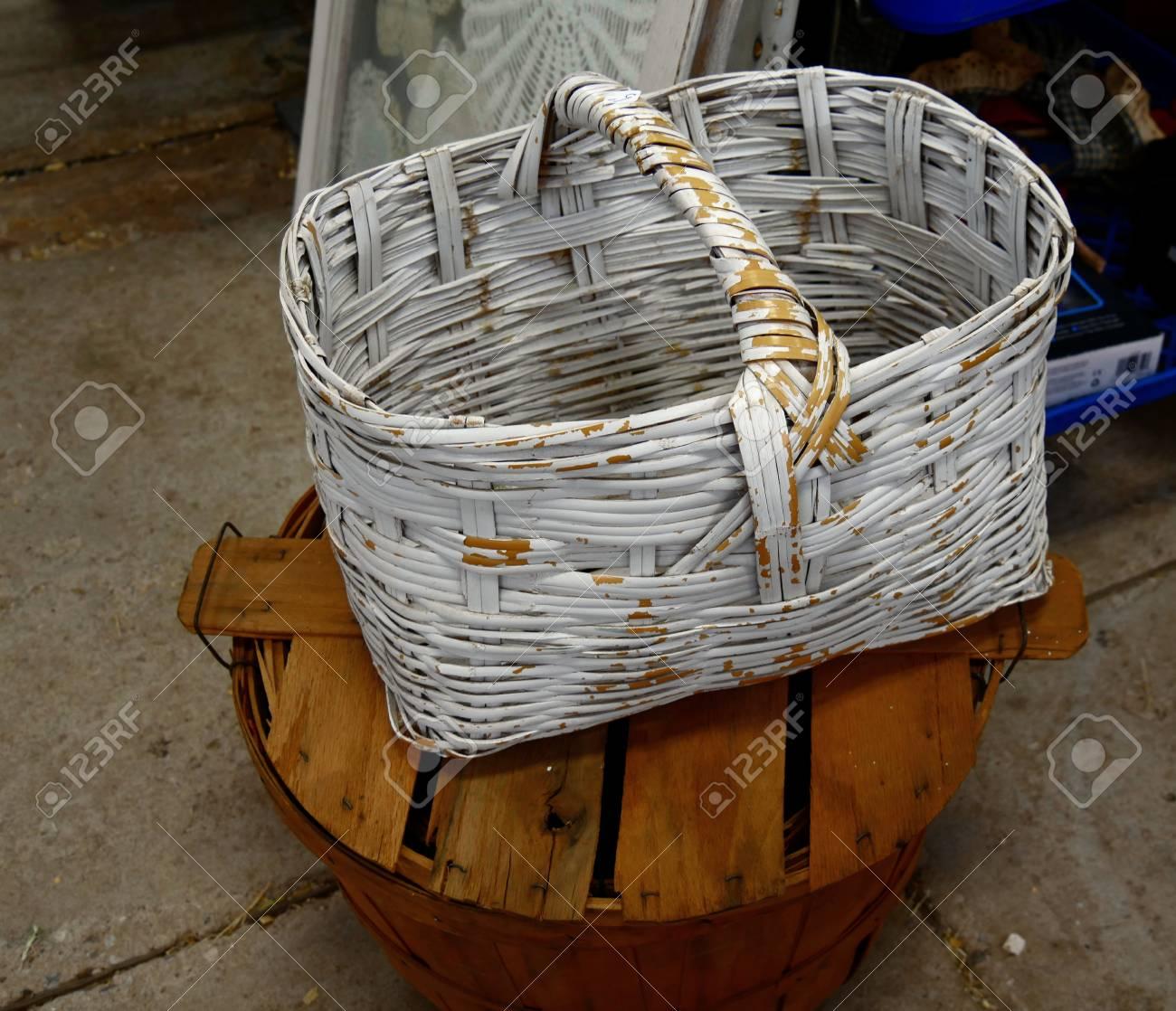 Peindre Un Panier En Osier panier en osier avec peinture blanche écaillée, posé sur un seau rond en  bois