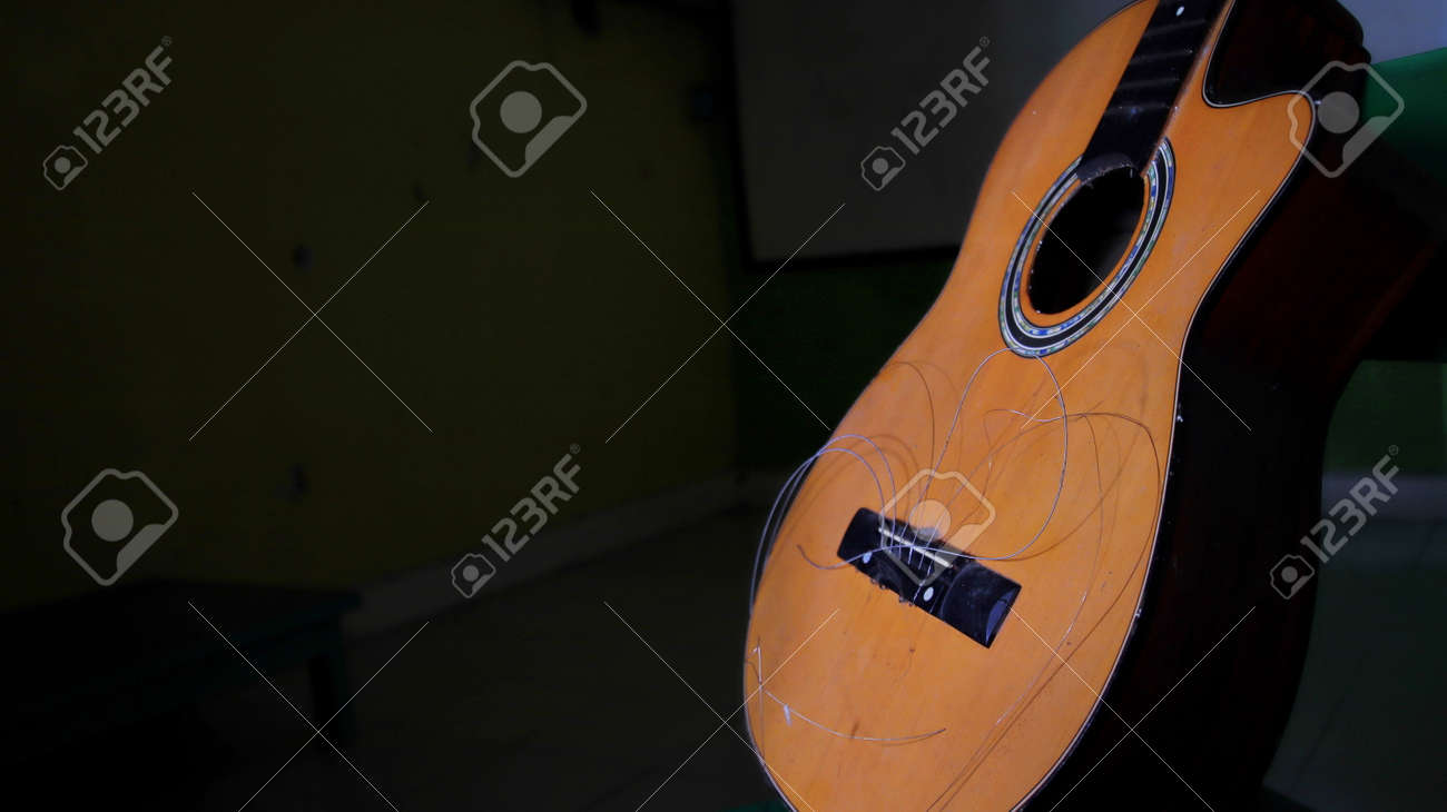 Not focus and noise image, damaged acoustic guitar, with the strings not attached, can't be plucked - 166878087