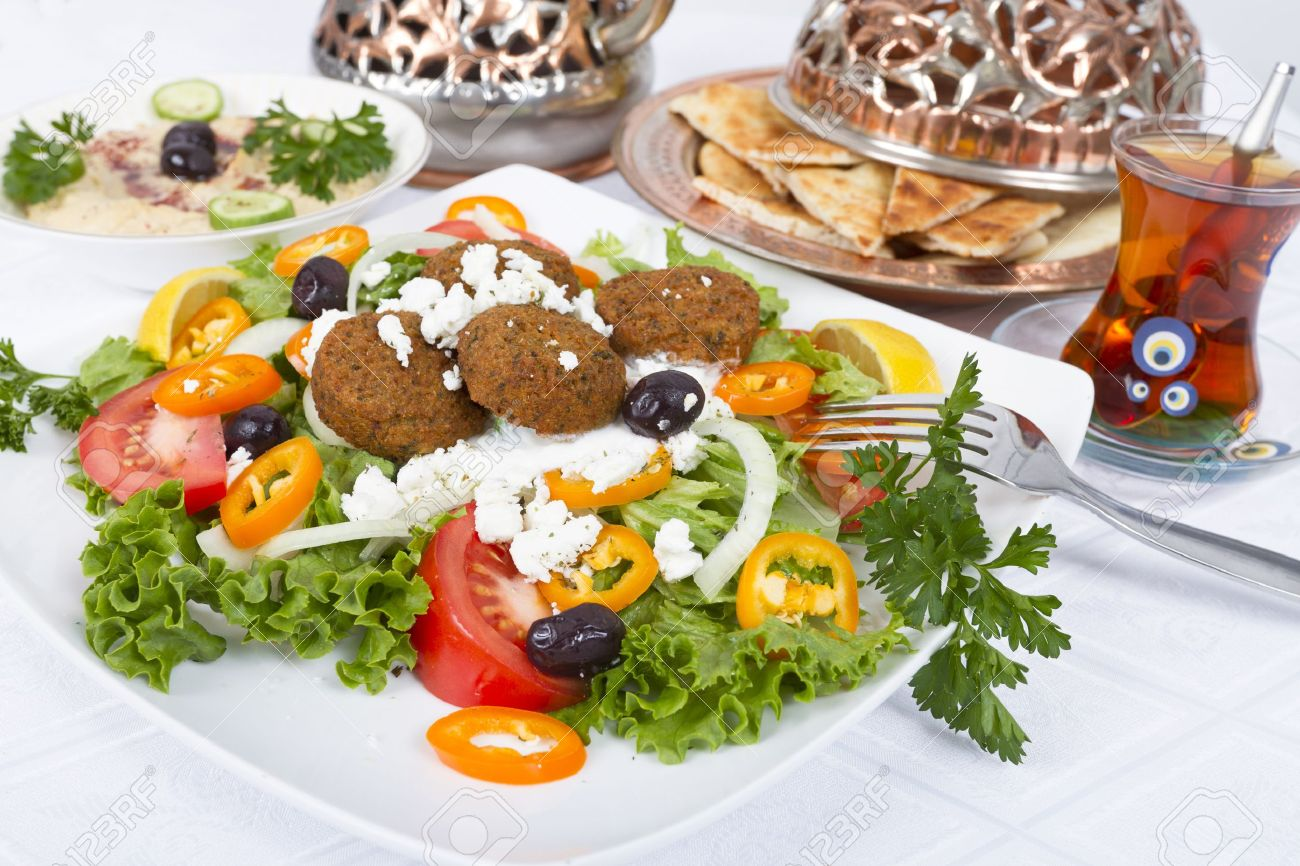 Falafel Salad with Pita Bread and Hummus plate, complimented with tea on a white table cloth. Stock Photo - 11967422