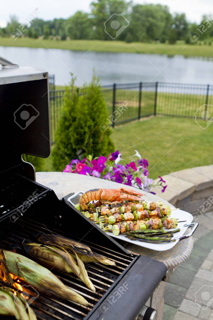 Mediterranean fish shish kebabs and lobster next to the BBQ right after cooked. Time for corns to be cooked. Stock Photo - 13992799