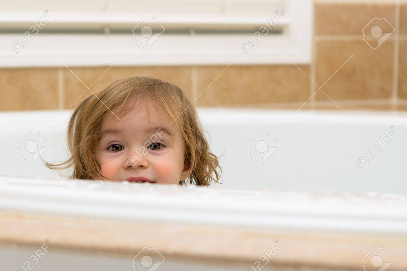 toddler girl giving happy hiding look from the bathtub, perhaps she is looking to take her bath Stock Photo - 18162533