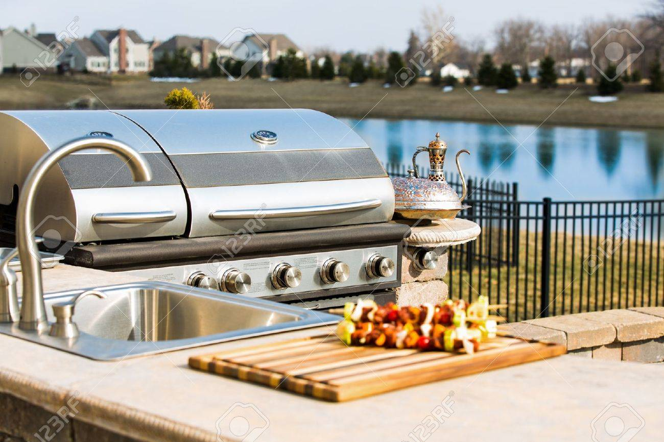 Bearbecue in outside kitchen along with sink and complimented with skewers and copper plate. Stock Photo - 18856959
