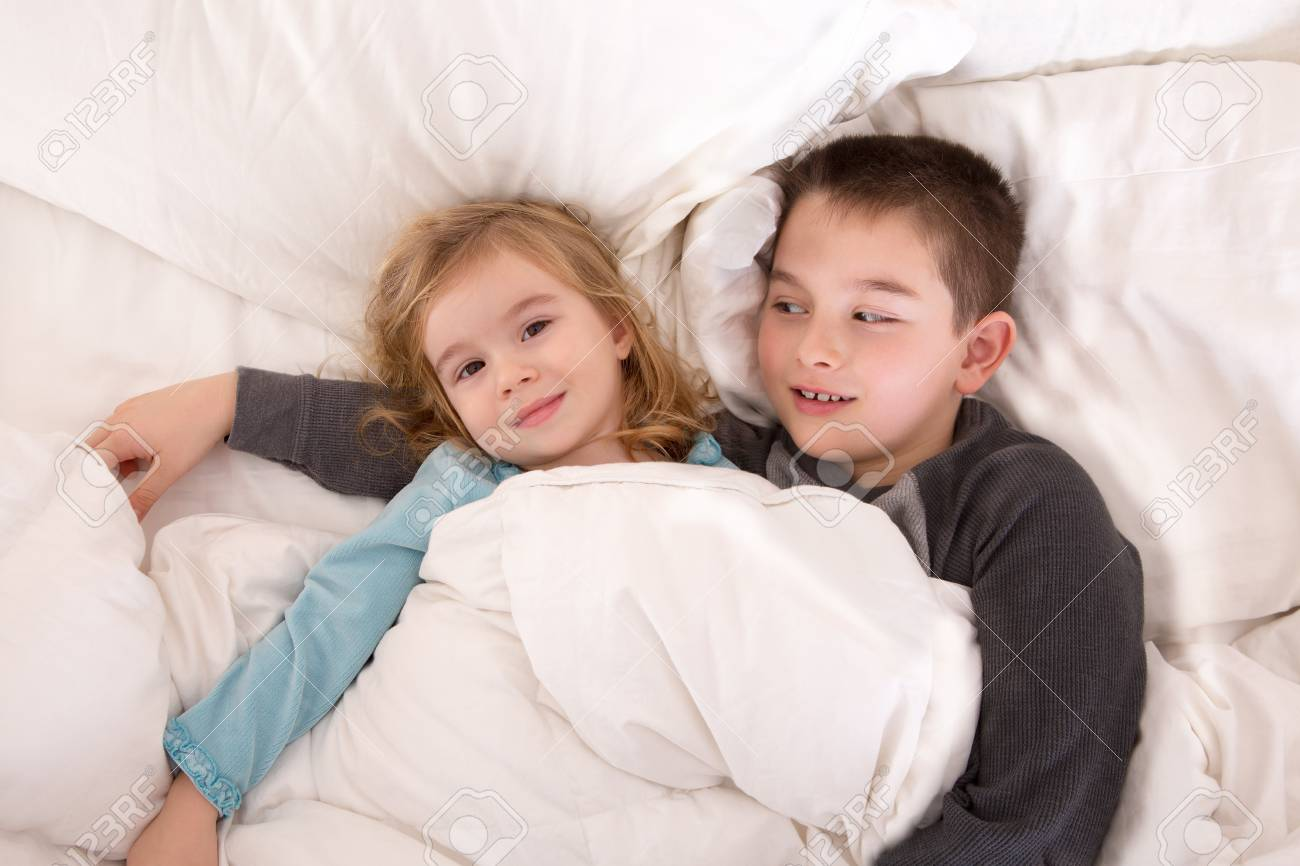 Protective young boy lying in bed with his little sister watching over her as she lies smiling up at the camera as they prepare to go to sleep Stock Photo - 25143729