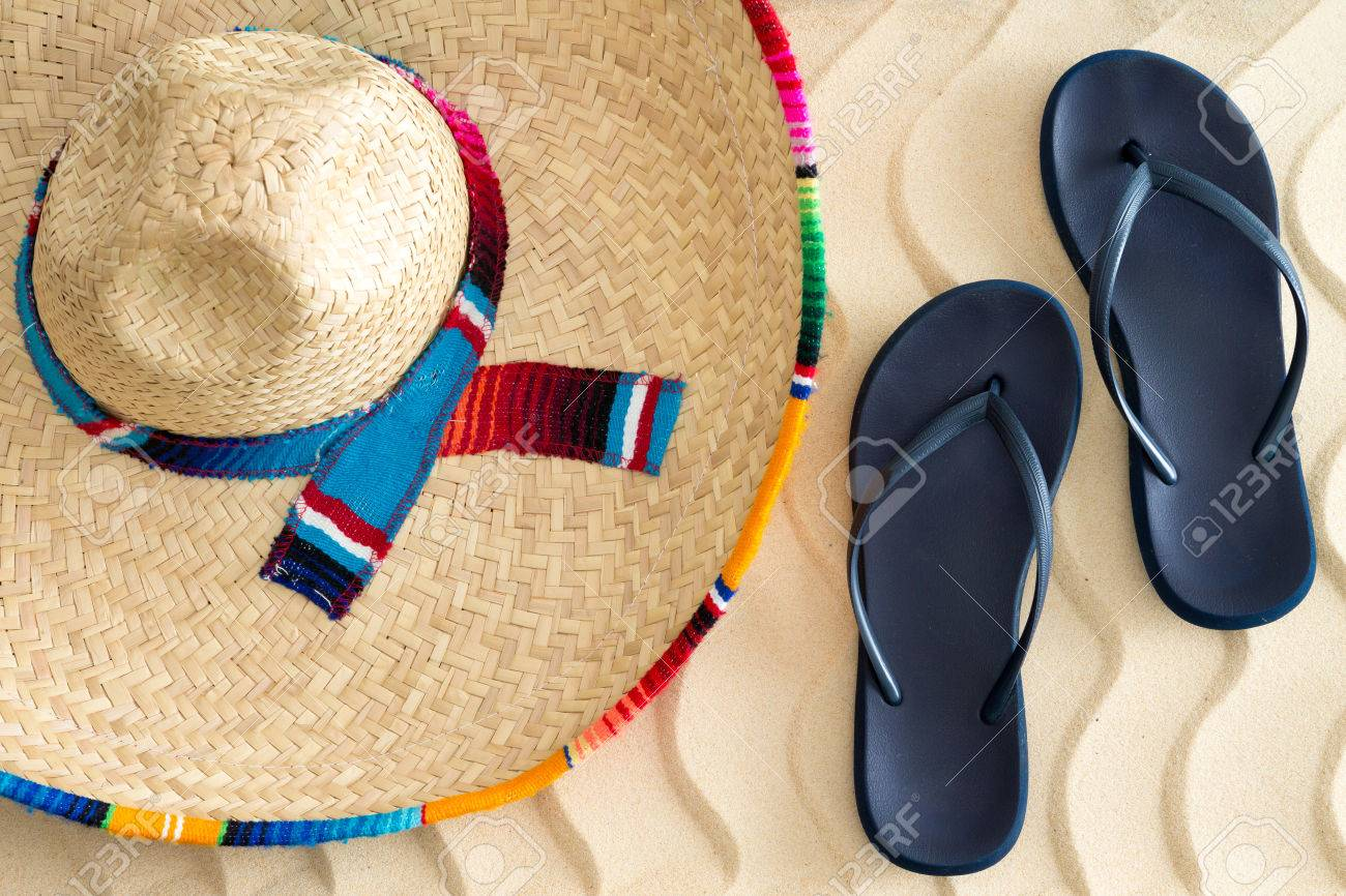 d850b91ca Stock Photo - Straw sombrero or sunhat with a colorful striped ribbon and  slip-slops or sandals on golden tropical beach sand with a wavy design  conceptual ...