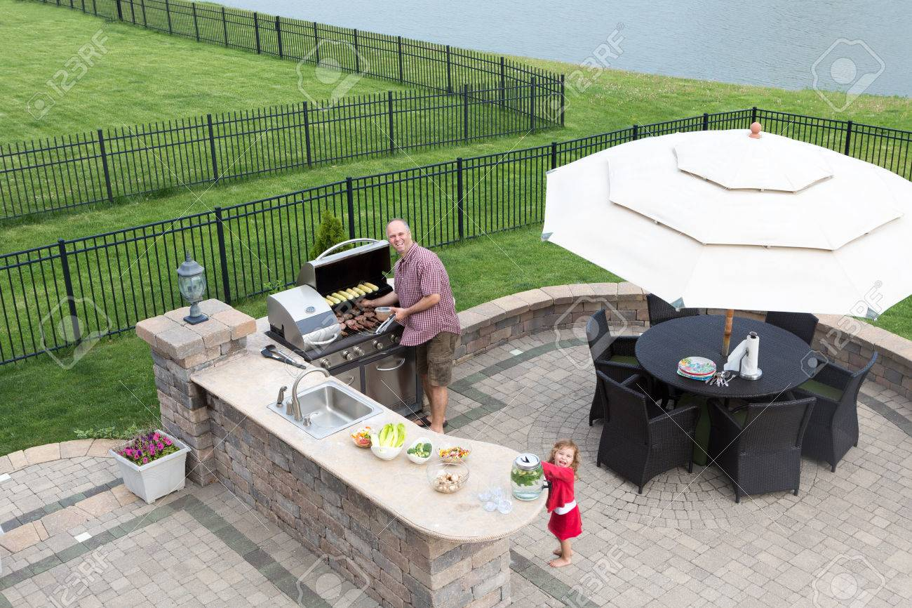 Outdoor Kitchen: Father And Daughter Preparing A Barbecue At An Outdoor  Summer Kitchen On A