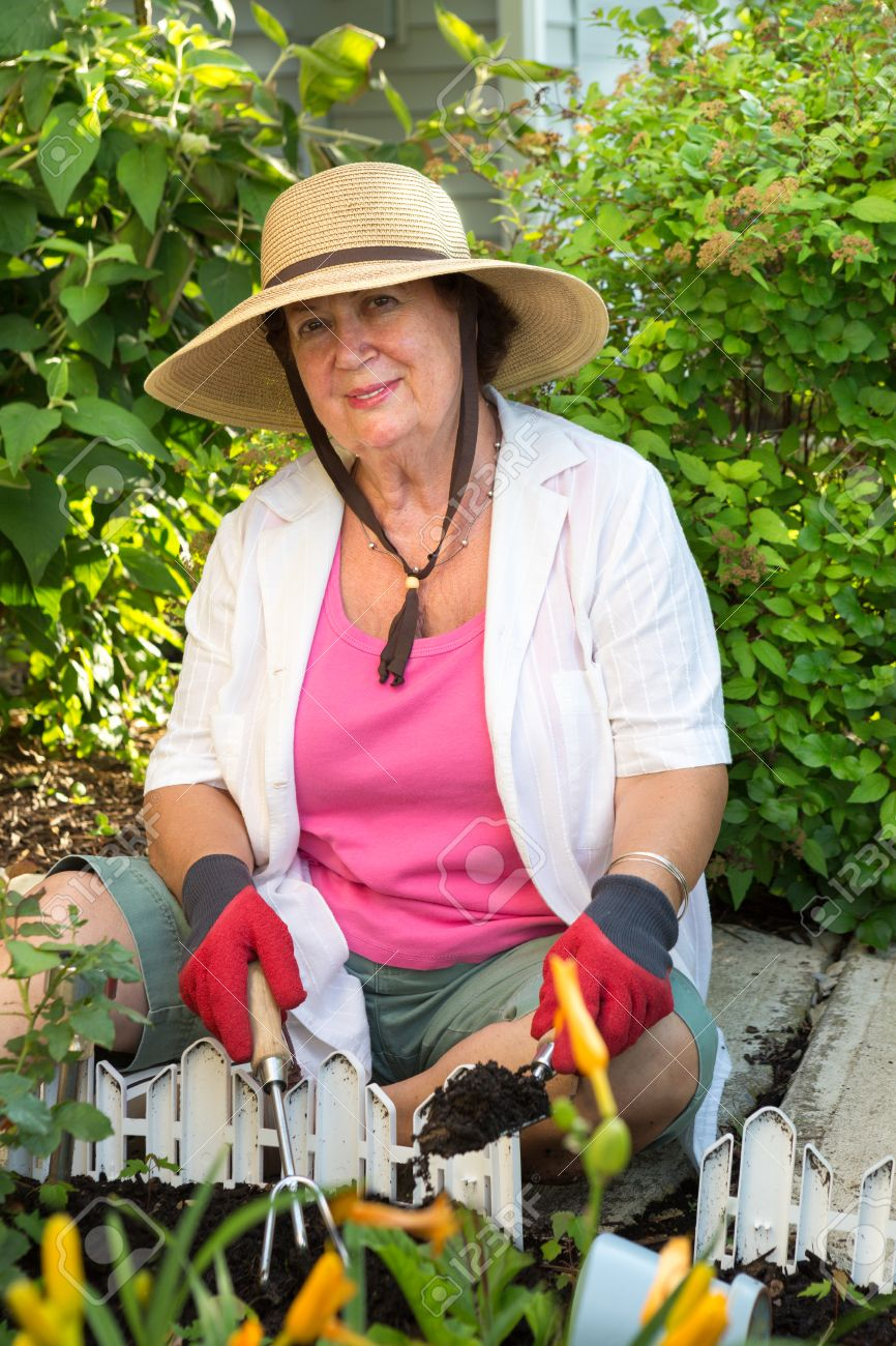 Senior Woman Smiling At Camera Wearing Straw Hat, Casual Clothes And  Gardening Gloves While Planting