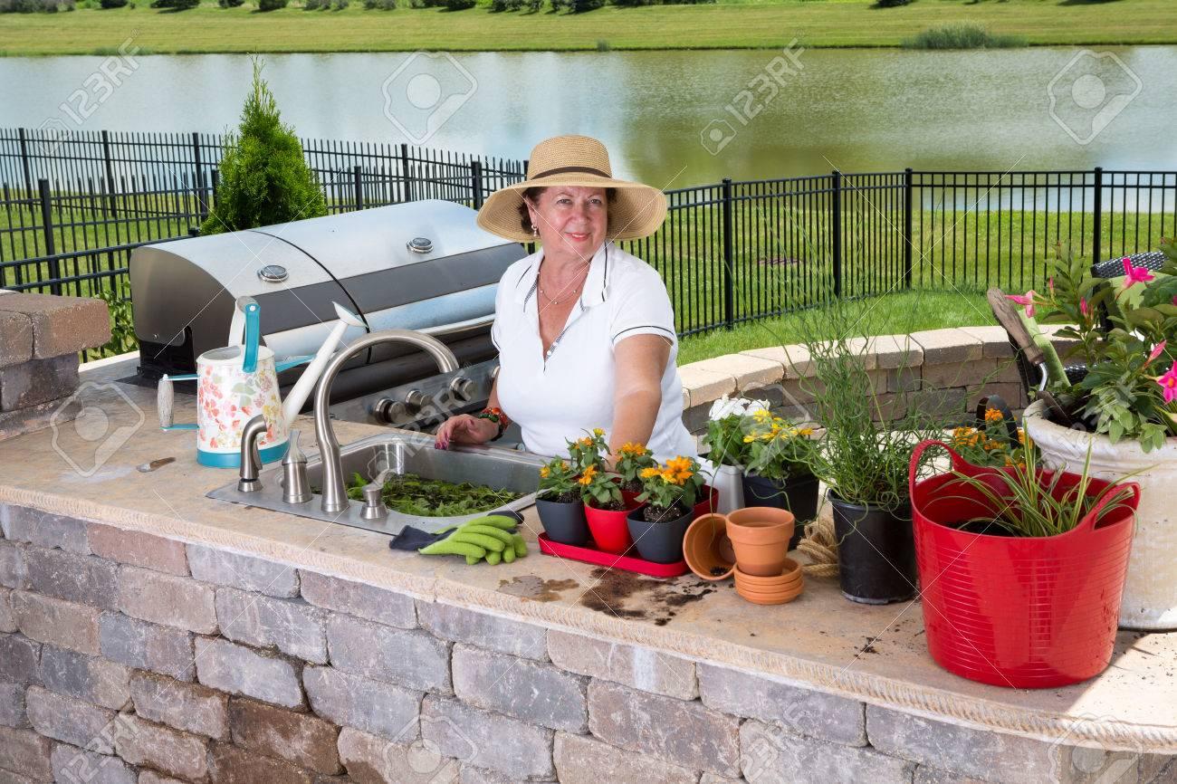 Sommerküche Waschbecken : Attraktive ältere frau die pflege ihrer zimmerpflanzen stand an der