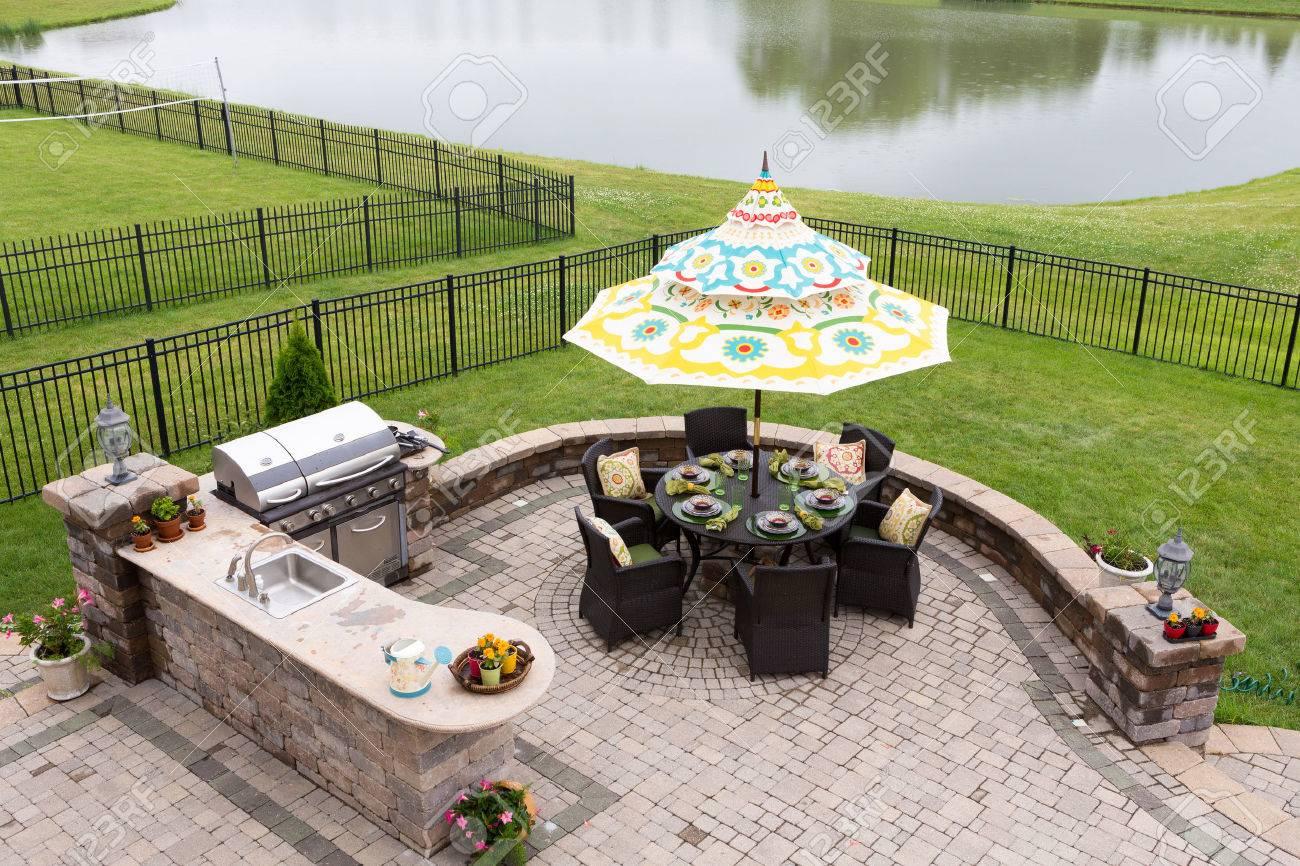 Utomhus boyta på en tegelsten uteplats med utsikt över en lugn sjö ...