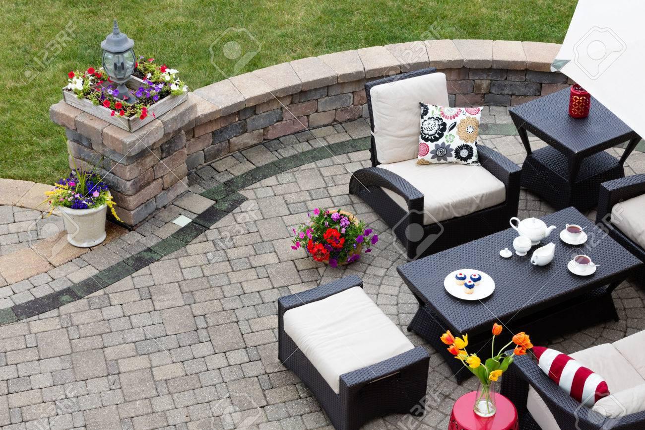 Pavée de briques terrasse avec mobilier de jardin confortable avec des  fauteuils modernes et un tabouret autour d\'une table dressée avec du thé et  des ...