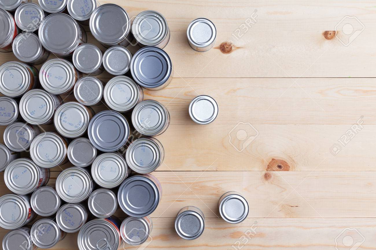 Conceptual background of multiple canned foods in sealed aluminum tins or cans of varying sizes arranged on a wooden table with copy space, overhead view - 50249941