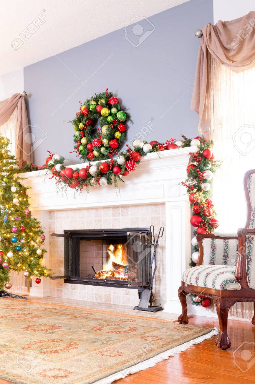 Festive Christmas Fireplace With Wreath, Colorful Garland , Decorated Tree  And Comfortable Armchair In Front