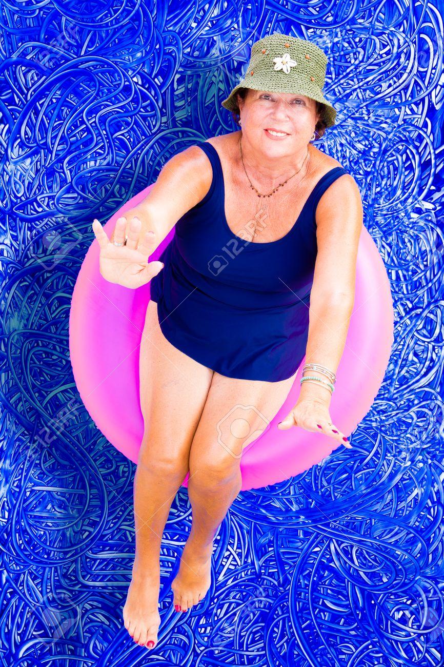Señora Mayor En Un Sombrero Elegante Y Traje De Baño Que Flota En Un Tubo  En La Relajante Piscina En Un Día Caluroso De Verano Mirando Hacia Arriba  Para ... c1e75e89a74