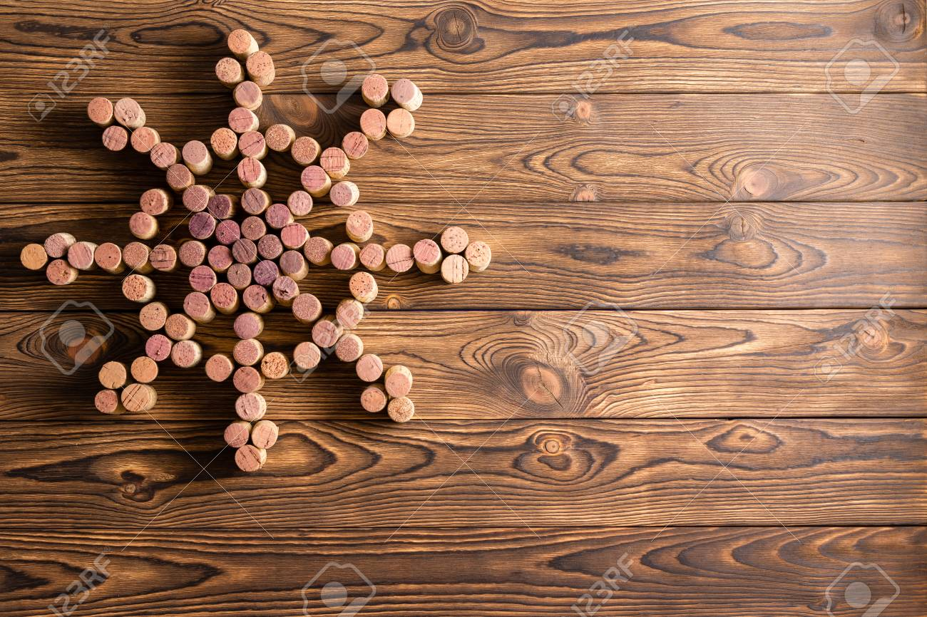 Banque dimages nautical themed wine cork design background with the bottle corks formed into a vintage ships wheel with spokes on a rustic wood