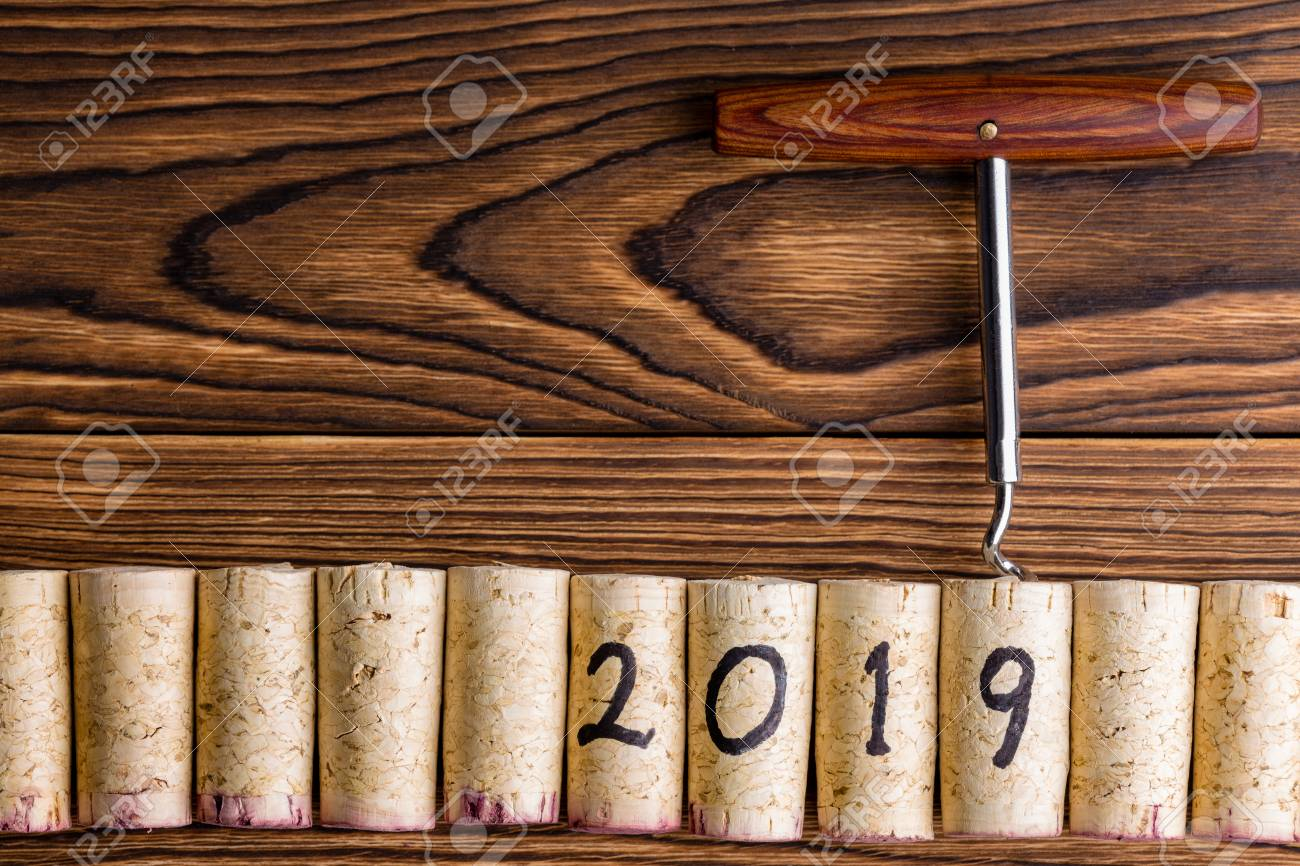 2019 new year background with wine corks and a bottle opener or corkscrew on a textured