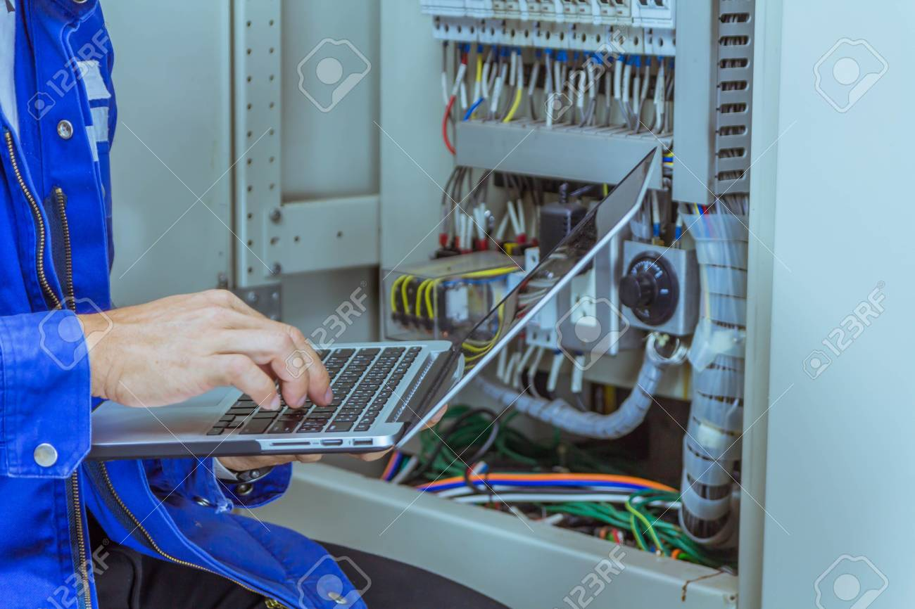 Male engineers are checking the electrical system by program in laptop. - 115599242