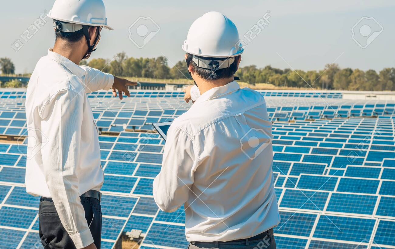 The solar farm(solar panel) with two engineers are talk about the production capacity, Alternative energy to conserve the world's energy, Photovoltaic module idea for clean energy production. - 144666689