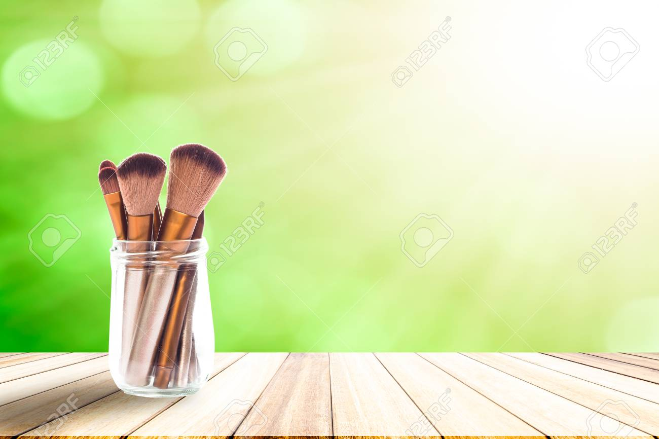 Set of cosmetic makeup brushes place in a glass jar on white wood floor table background
